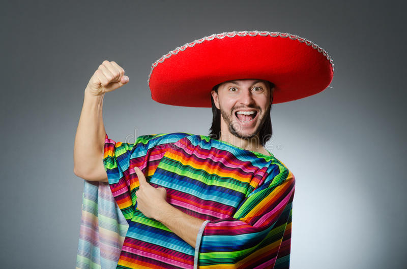 The man in a vivid mexican poncho gray background isolated stock photos