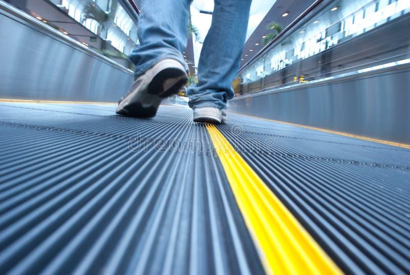 Man voet die in luchthavenroltrap loopt stock fotografie