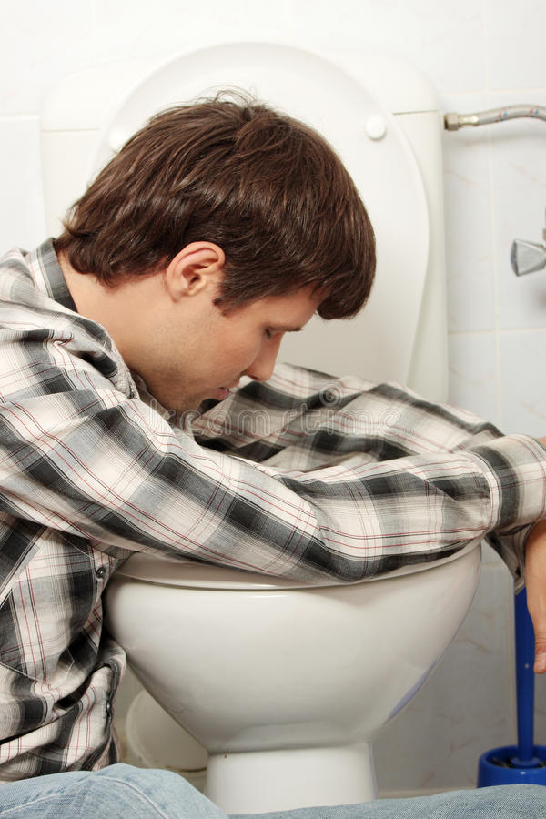 Man vomiting. Young man (drunk or sick) vomiting stock image