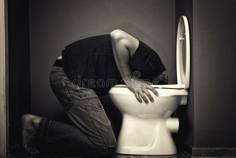 Man vomiting. In toilet bowl stock photos