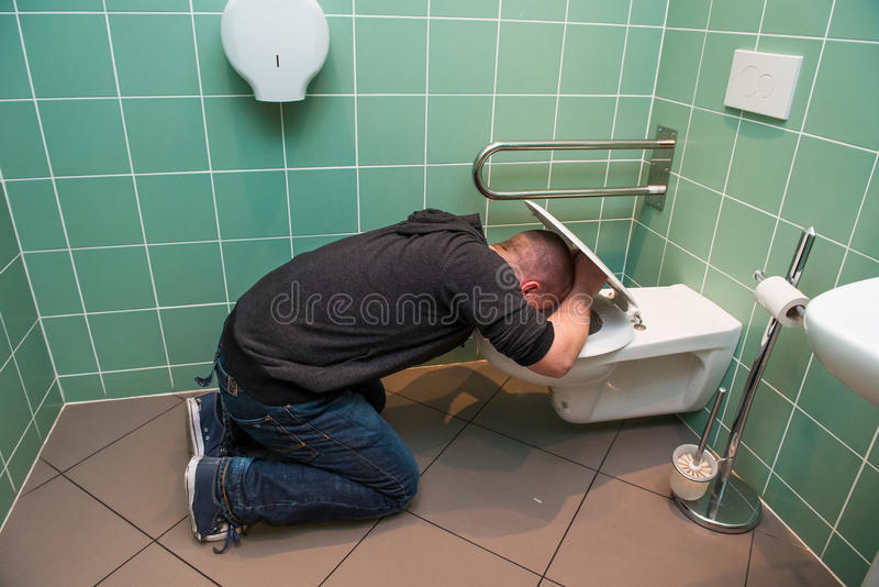 Man vomiting in the toilet. Man kneeling and vomiting in the toilet royalty free stock photo