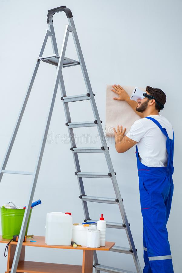 The man with vr glasses gluing wallpaper. Man with VR glasses gluing wallpaper royalty free stock photos