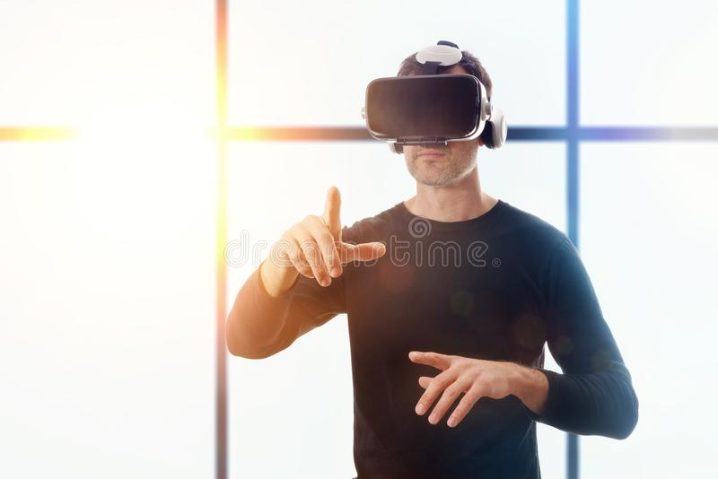 Man with vr glasses pointing with his finger window background stock image