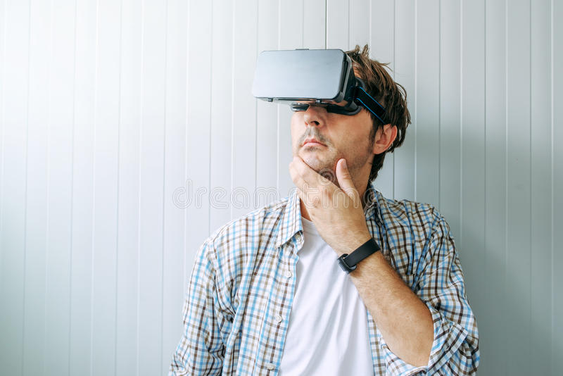 Man with VR goggles exploring virtual reality econtent. Man with VR goggles exploring virtual reality content and enjoying in cyberspace environment royalty free stock image