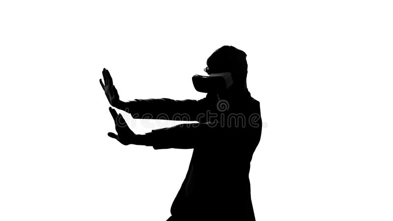 Man in vr headset having dangerous trip in virtual reality, overcome obstacles stock images