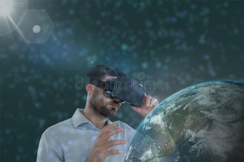 Man in VR headset looking to a 3D planet against green background with flares stock illustration