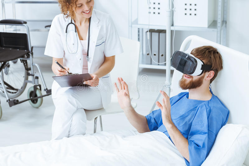 Man in VR during therapy. Young men in VR gesticulating during therapy in hospital royalty free stock photos