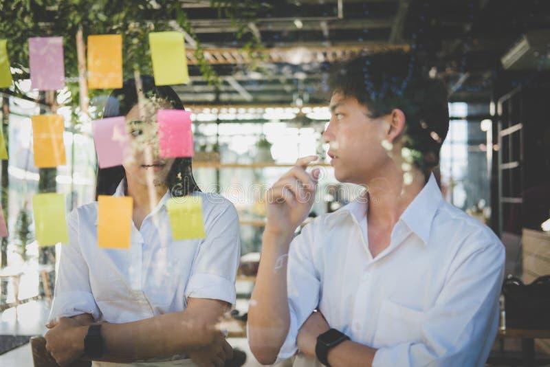 Man & vrouw die creatief idee bespreken met zelfklevende nota's over glas stock foto's