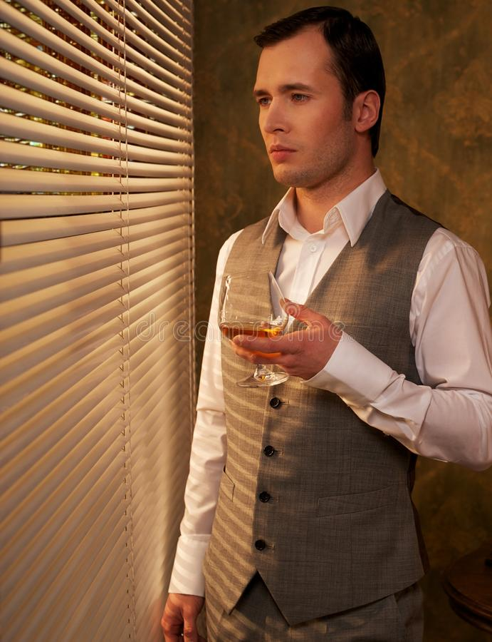 Man in waistcoat with glass stock image