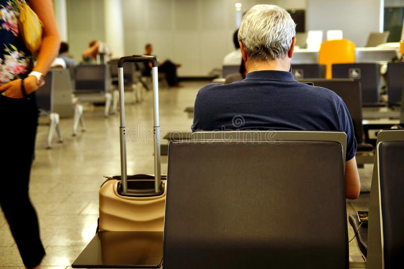 A man waiting at airport lounge for plane. Entrepreneur sitting at airport business lounge. royalty free stock photos