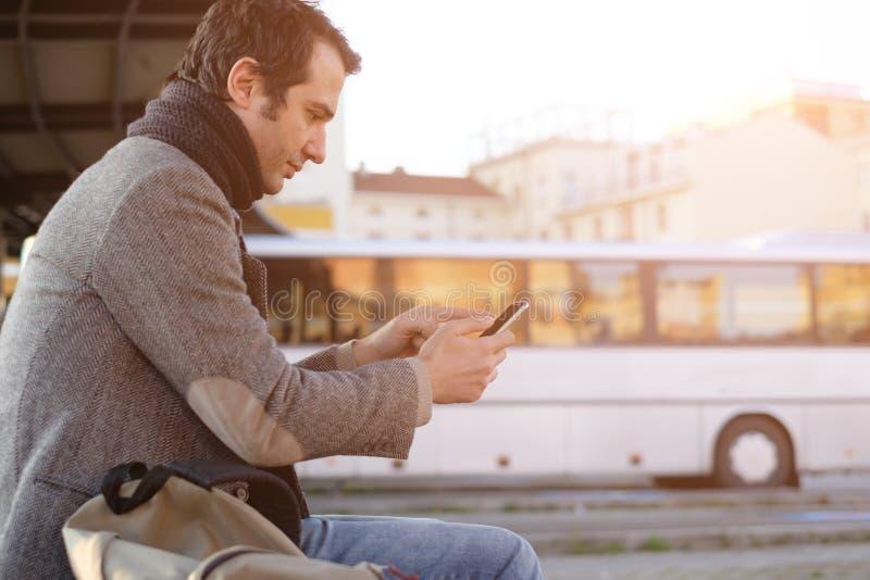 Man waiting at the bus station and looking at his smart-phone stock photo
