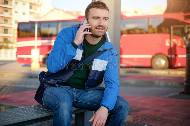 Man waiting at the bus station and looking at his smart-phone royalty free stock images