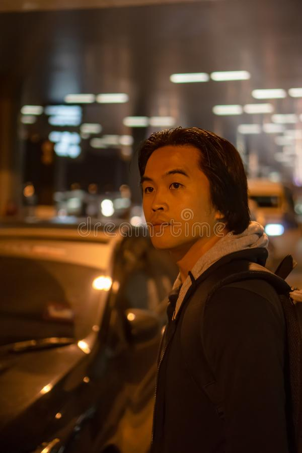 Man waiting for his car ride. Asian man waiting for his car ride at night in an airport royalty free stock images