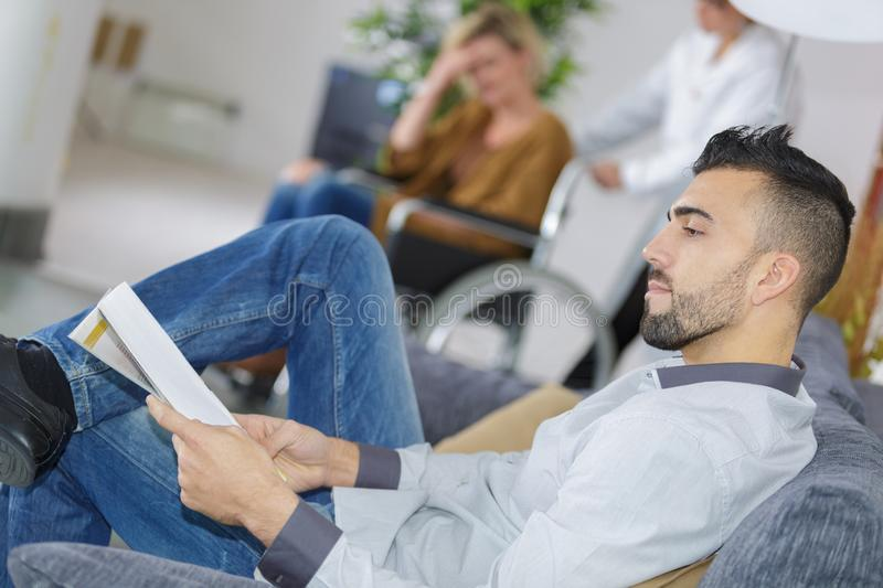 Man in waiting room as patient gets pushed along in wheelchair stock photo
