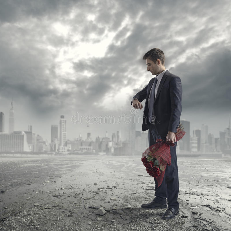 Man waiting with roses. Elegant man waiting for a date with red roses on futuristic metropolitan background royalty free stock image