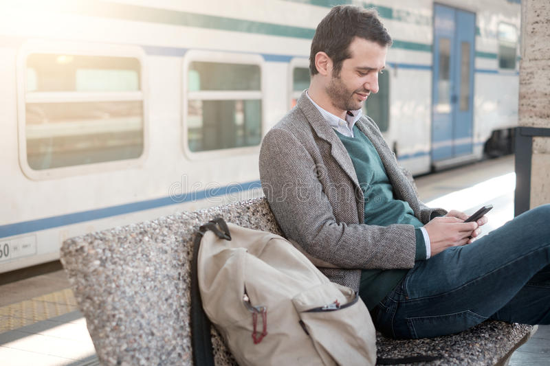 Man waiting for the train seated in a train station stock photos