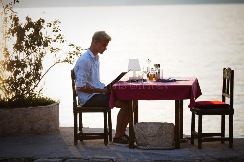 Young man waiting for woman in restaurant royalty free stock images