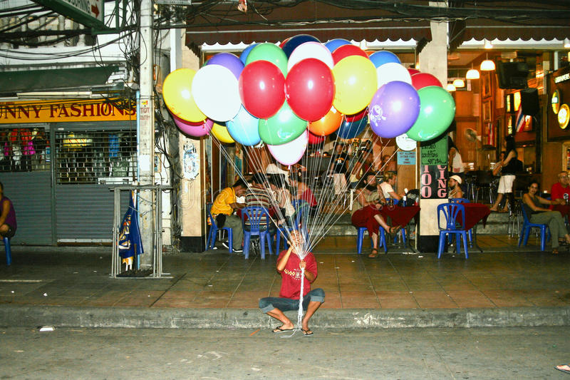 Man waits for tourists in Khaosan. BANGKOK - DECEMBER 3: Man waits for tourists in Khaosan Road to sell balloons on December 03, 2006 in Bangkok. Khaosan Road is stock photo