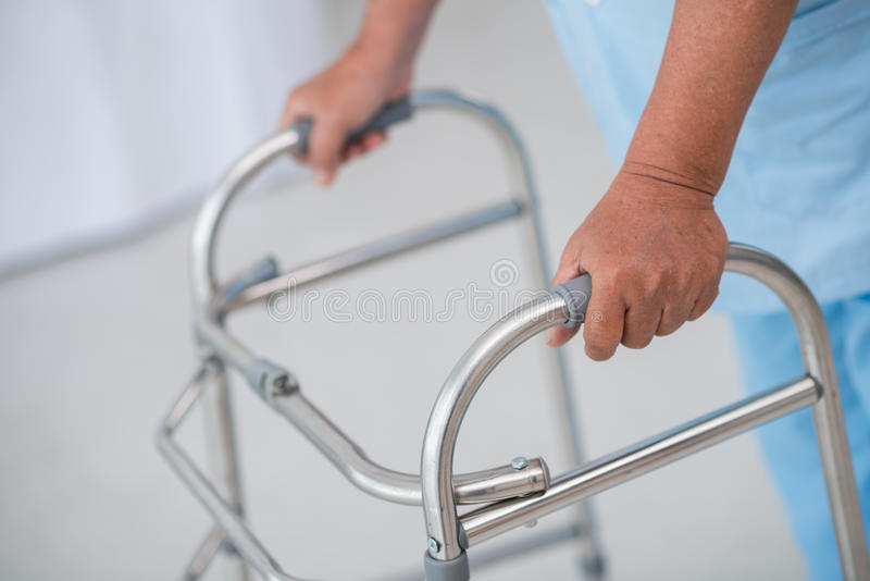 Man with walker. Close-up of male patient moving with walker royalty free stock image