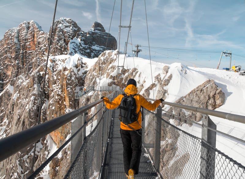 Man walking across rope bridge on Dachstein mountain royalty free stock photo