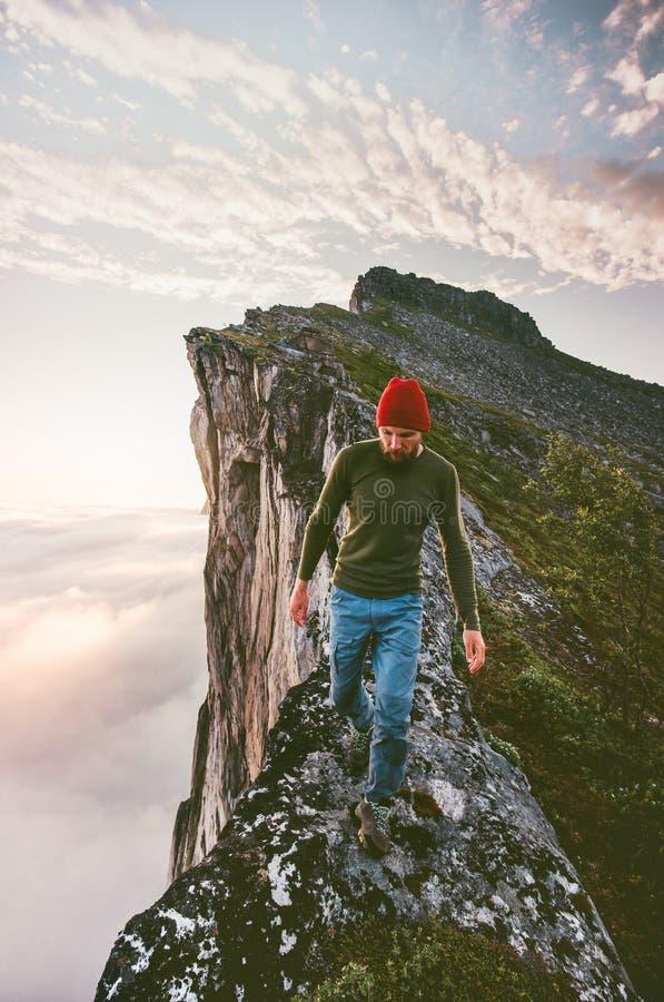 Man walking alone on the edge mountain ridge stock images
