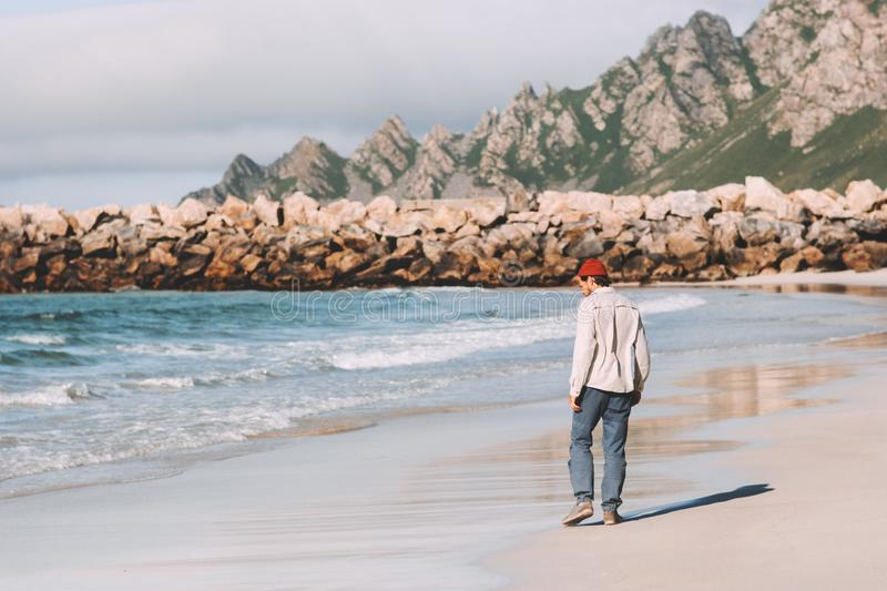 Man walking alone on empty beach traveling in Norway. Active vacations outdoor lifestyle adventure weekend trip stock image
