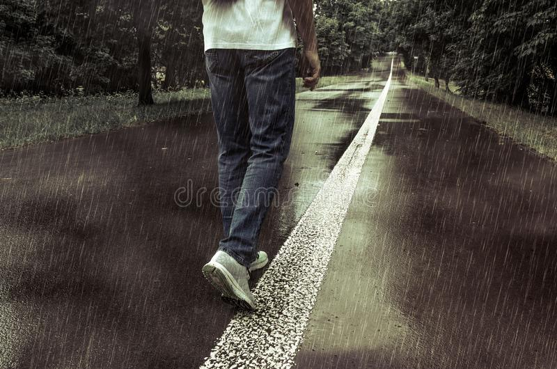 A man walking alone in the rain on a park alley royalty free stock photos