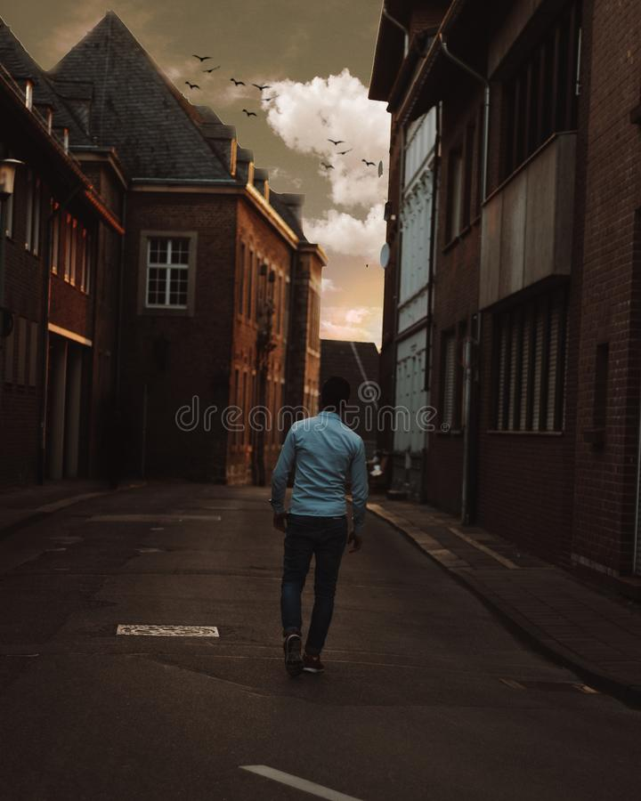 Man Walking Alone in the Street of Town stock photos