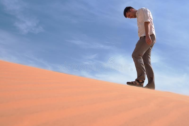 Man walking alone in the sunny desert. He is lost and out of breath. No water and energy. royalty free stock photo
