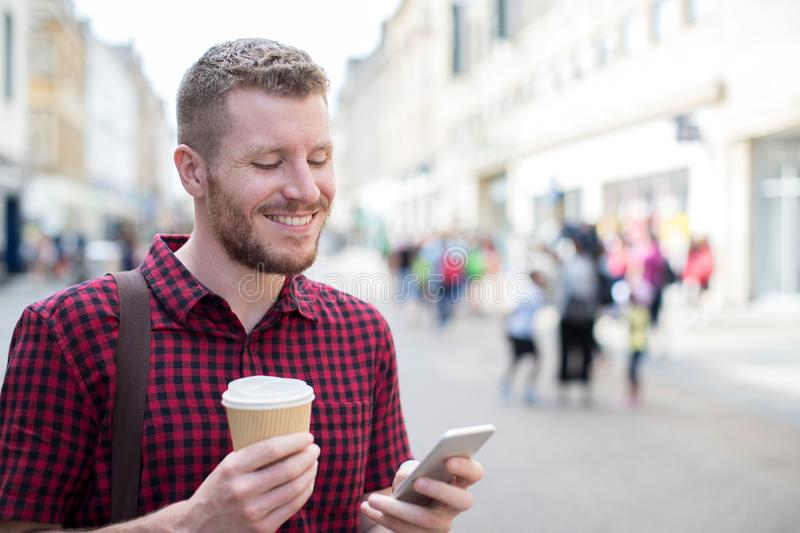 Man Walking Along City Street Reading Text Message On Mobile Phone stock images