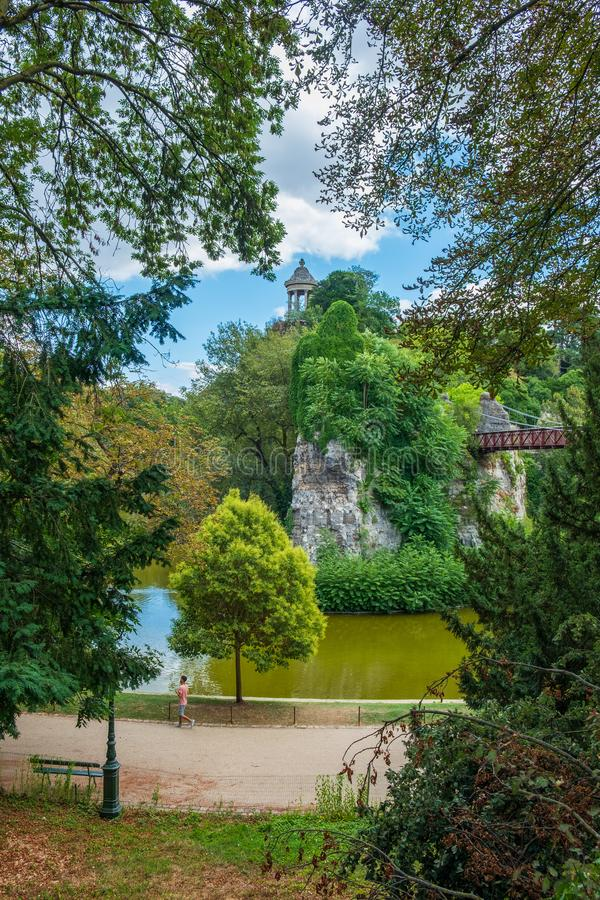 Man walking along a path at park Parc des Buttes-Chaumont in P royalty free stock images