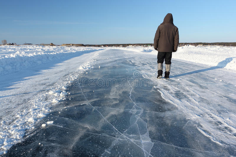Man walking along a road of ice on the frozen reservoir stock image