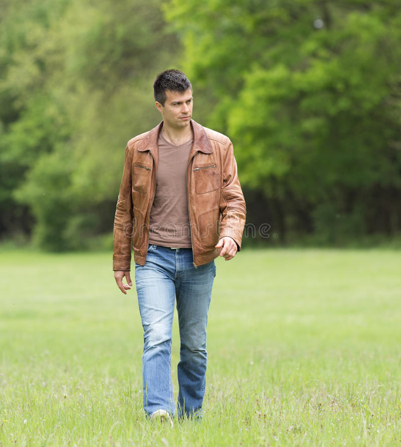 Man walking. Attractive young man walking alone in forest stock photos