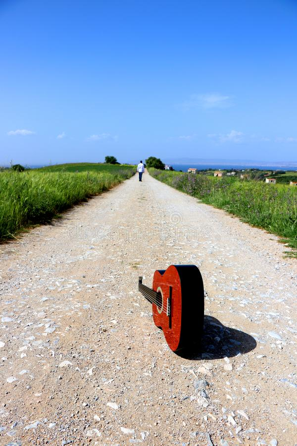Man walking away. Brown classic guitar on the country road stock photos
