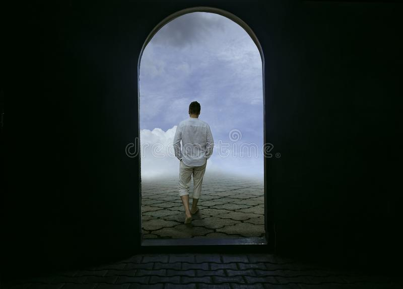 Man Walking Away from Dark Prison to Bright Future stock photography