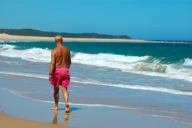 Man walking on beach. A single elderly caucasian man walking in the water on a lonely beautiful beach by the Indian Ocean in South Africa. He is enjoying his royalty free stock photography