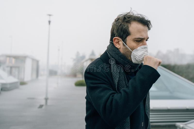 Man wearing protection mask against traffic smog air stock image