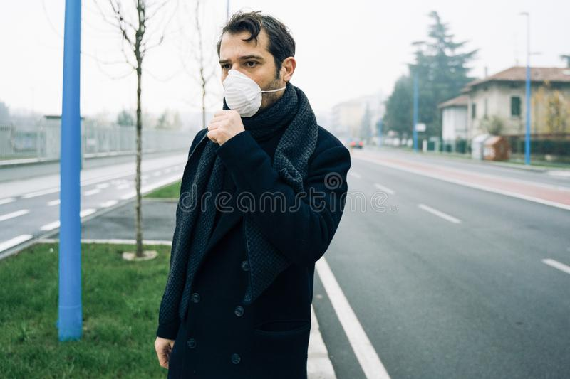 Man walking in city wearing mask against smog air pollution stock photography