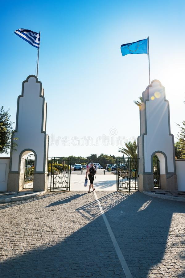Man walking in between the columns with flags in Kallithea Rhod. Es, Greece stock photos