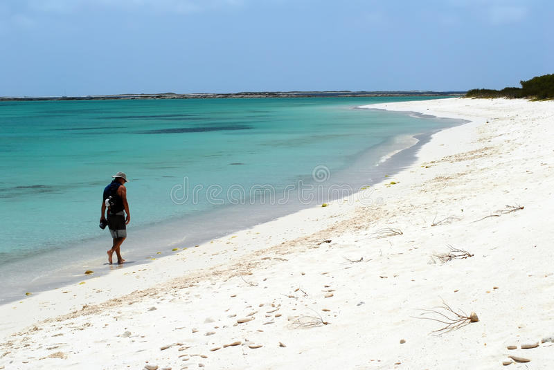 Man walking on deserted white beach stock photography