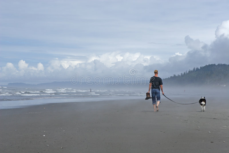 Man walking Dog on Beach. Man walking his dog on Kalaloch Beach in stormy weather royalty free stock photography