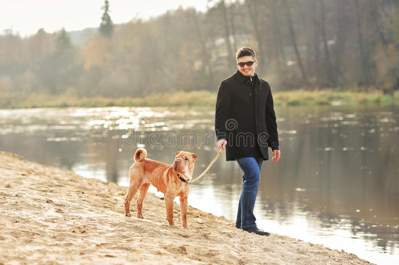 Man walking with dog near the river. Outdoors royalty free stock image