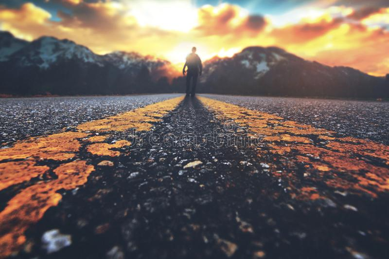 Man walking down road. A man walking down a road towards a mountain sunset royalty free stock photos