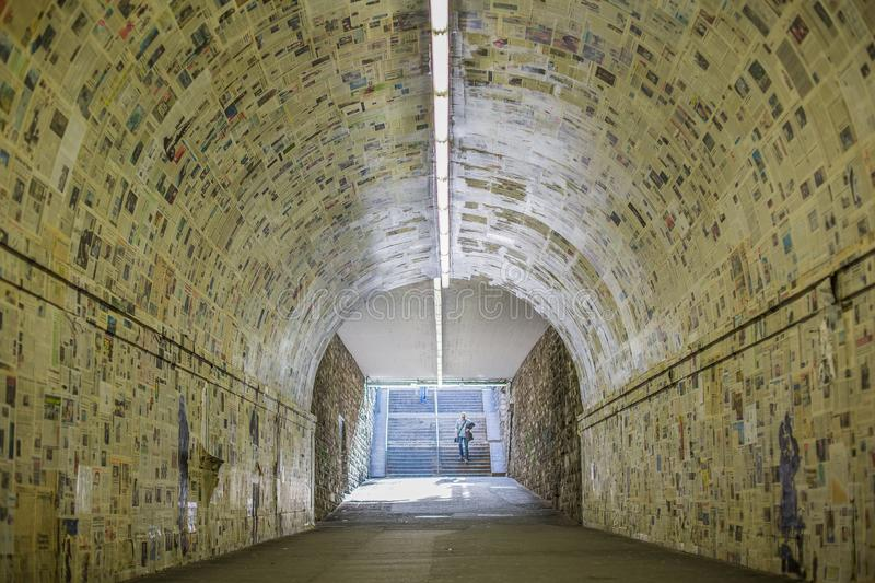 A man is walking down to the tunnel which be patched with newspaper art - Lugano, Switzerland stock photo