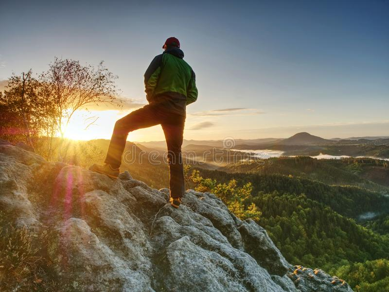 Man walking on the edge of a cliff at summit. Hrensko range. Czech Republic 21st of Seprtember 2018. Climber enjoying beautiful nature view at sunset after stock photography