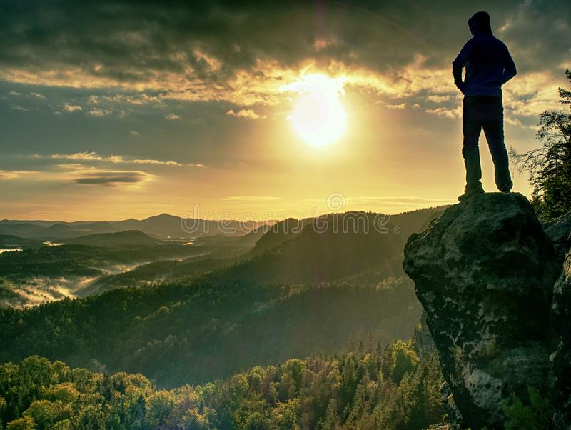 Man walking on the edge of a cliff at summit. Hrensko range. Czech Republic 21st of Seprtember 2018. Climber enjoying beautiful nature view at sunset after stock image
