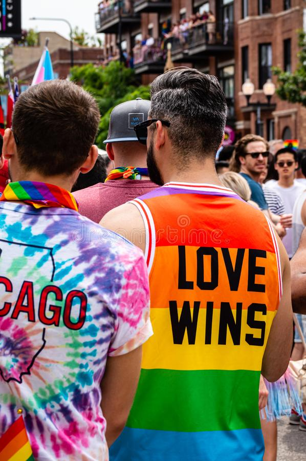 Man walking with friends at Gay Pride parade is wearing a rainbow colored shirt that reads `Love Wins`. Boystown, Chicago-June 30, 2019: Man walking with friends royalty free stock photos
