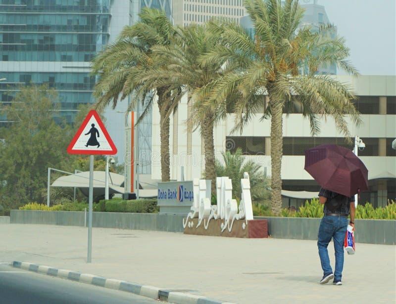 Man walking in front of Doha bank Qatar royalty free stock photography