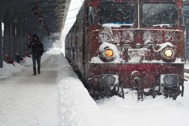 Man walking by a frozen train locomotive. Bucharest, Romania - January 7, 2017: Front view of young Caucasian man walking past a frosty passenger train stock images