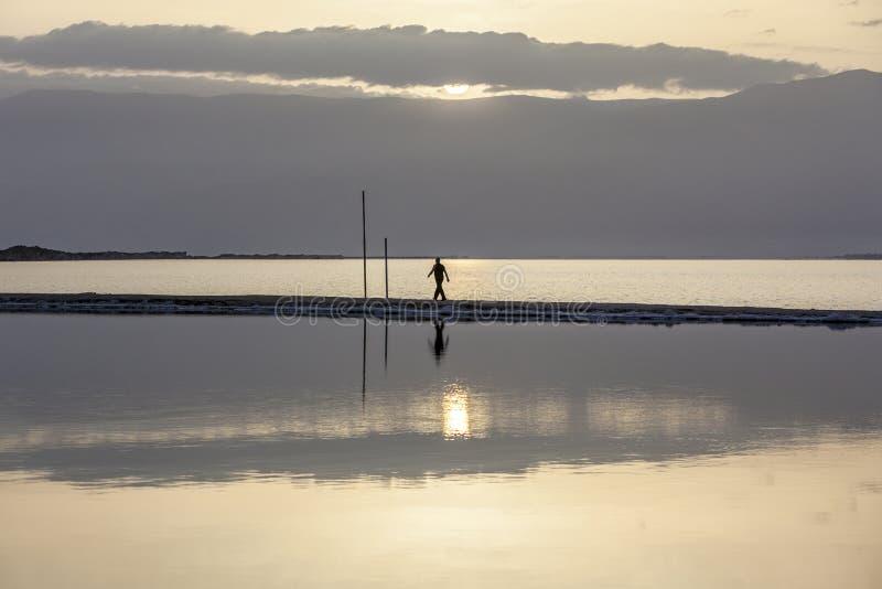 Man walking on headland at early morning under rising sun. Man wearing black sports clothes walking on headland at the Dead Sea in early morning under rising sun stock photography